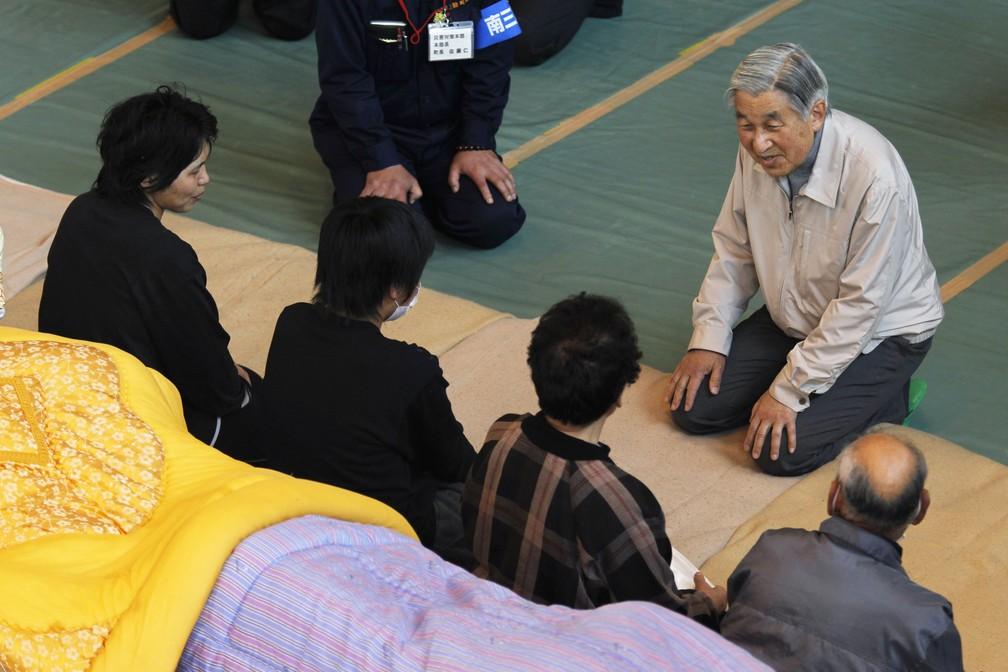 """O imperador Akihito se ajoelha para falar com pessoas desabrigadas pela tragédia em Fukushima, em 2011. O gesto foi visto como """"um grande símbolo de compaixão com o sofrimento daquelas pessoas"""", segundo a BBC. — Foto: HIRO KOMAE / POOL / AFP"""