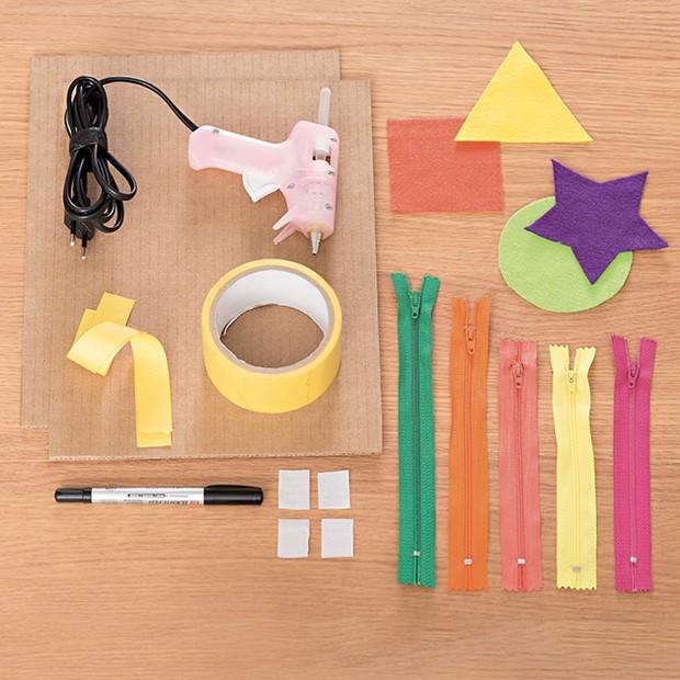 1. Material: 2 placas de papelão (30 cm x 20 cm) / Cola quente / Feltros em formas geométricas / Fita de tecido / Fita adesiva (5 cm) / Zíperes / Velcro / Caneta (Foto: Bruno Marçal / Editora Globo)