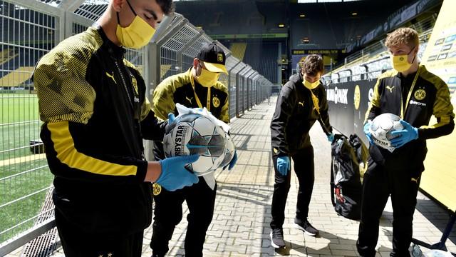 Gandulas do Borussia Dortmund desinfectam bolas antes da partida