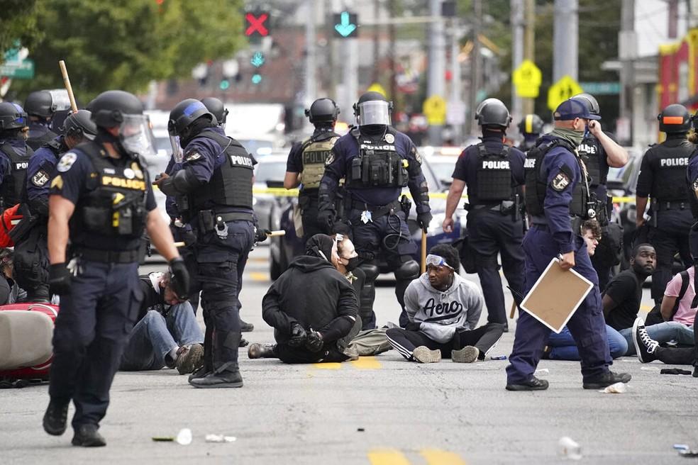 Manifestantes se sentam nas ruas de Louisville após serem detidos em protesto nesta quarta-feira (23) contra decisão judicial que livrou policiais de acusações de envolvimento direto na Breonna Taylor — Foto: John Minchillo/AP Photo
