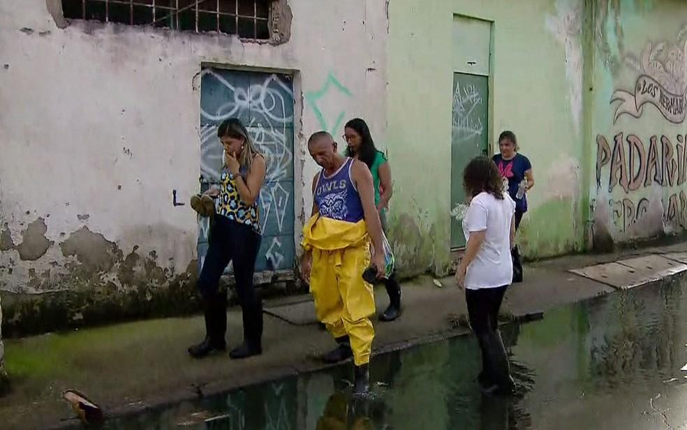 Moradores usam galochas para conseguir andar pelas ruas do bairro — Foto: Reprodução/TV Globo