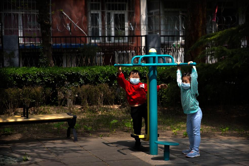 Crianças com máscara brincam em parque de Pequim, nesta terça-feira (7)   — Foto: Mark Schiefelbein/AP