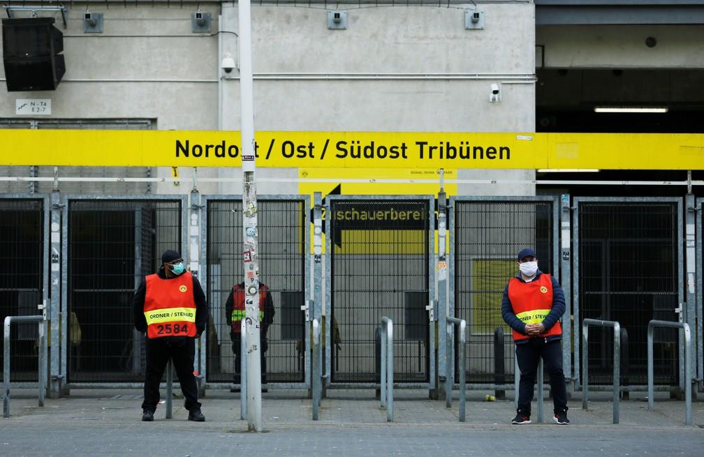 Seguranças à frente de portões fechados para o público no Signal Iduna Park antes do clássico entre Borussia Dortmund e Schalke 04 — Foto:  REUTERS/Leon Kuegeler