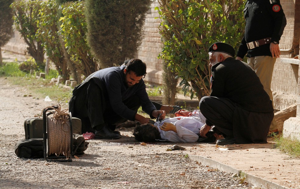 Polícia retira armas de homem que participou de ataque a uma faculdade de Peshawar nesta sexta-feira (1º)  (Foto: Fayaz Aziz/ Reuters)