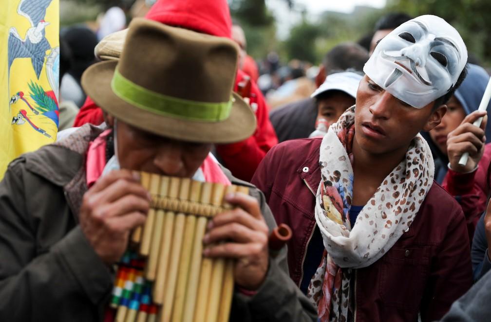 Manifestantes usam máscaras e tocam instrumentos típicos durante protestos em Quito, no Equador — Foto: Ivan Alvarado/Reuters