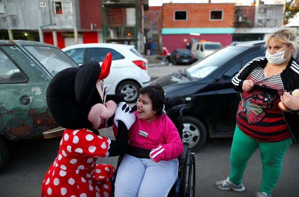 Vestida de Minnie, voluntária abraça jovem no bairro de Fuerte Apache, em Buenos Aires, no domingo (16) — Foto: Agustin Marcarian/Reuters