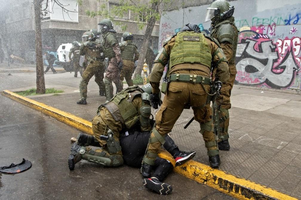 Manifestante é preso por polícia de choque durante protesto de indígenas no centro de Santiago em 10 de outubro  — Foto: Martin Bernetti/AFP
