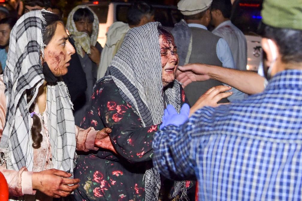 Mulheres feridas chegam a um hospital para tratamento após duas explosões no aeroporto de Cabul, no Afeganistão, nesta quinta (26)  — Foto: Wakil Kohsar/AFP