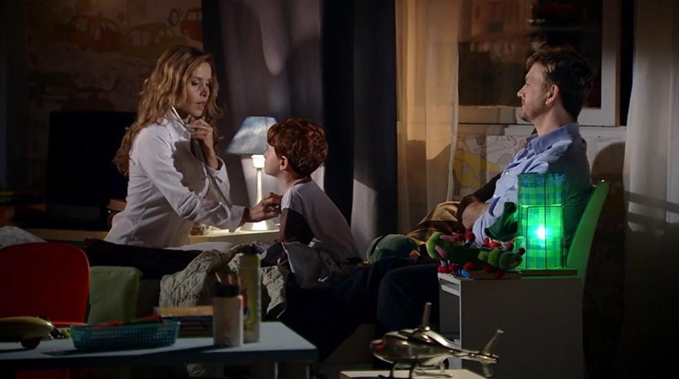 Celina (Leona Cavalli) cuida do menino e passa uma receita para o pai, que acompanha tudo com atenção — Foto: Globo