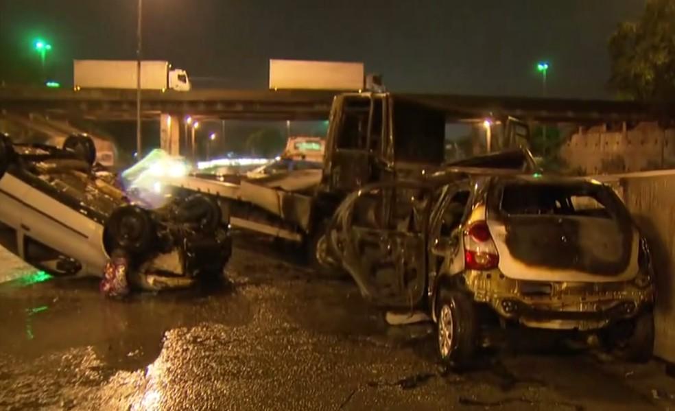 Caminhão-reboque cruzou a pista e atingiu os carros na Avenida Brasil, que pegaram fogo na hora (Foto: Reprodução/ TV Globo)