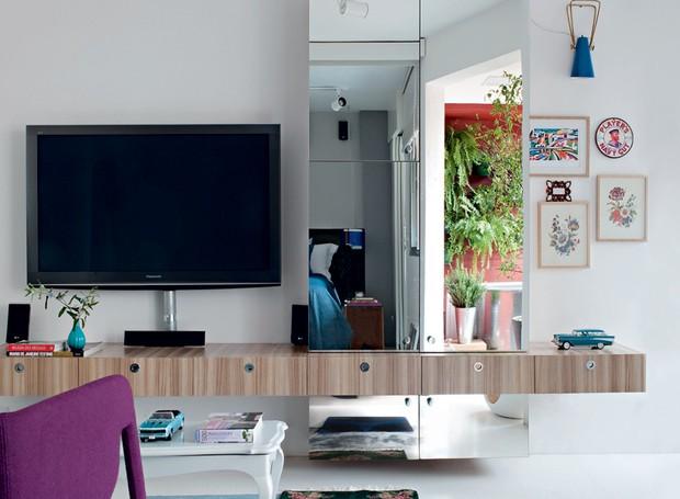 A marcenaria espelhada desta sala de TV executada pela Marcenaria Artifície transformou este apê de apenas 42 m². Projeto do designer de interiores Gabriel Valdivieso e da arquiteta Carolina Pereira (Foto: Marcelo Magnani/Editora Globo)