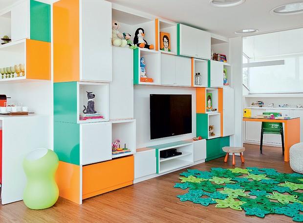 No quarto de lazer para as crianças, a arquiteta Madá Campos projetou uma estante. Os módulos coloridos organizam os brinquedos. No fundo, há uma bancada de trabalho para os pais estarem sempre por perto (Foto: Maíra Acayaba/Editora Globo)