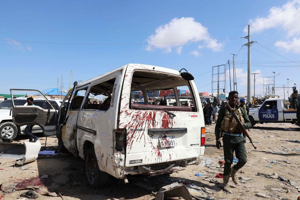 Policial somali ao lado de um veículo atingido pelo atentado — Foto: Feisal Omar/Reuters