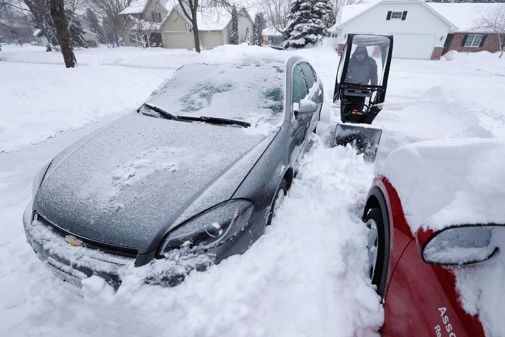 -  Homem retira neve acumulada entre veículos nesta segunda-feira  16  , em Appleton, Wiscosin  EUA   Foto: Dan Powers/The Post-Crescent via AP