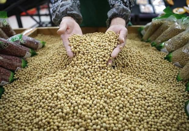 Funcionário escolhe grãos de soja em mercado de Wuhan, China (Foto: Reuters)