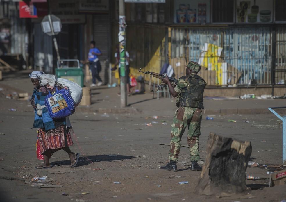 Soldado armado patrulha ruas de Harare enquanto mulher passa carregando sacolas; Zimbábue tem dia de protestos e repressão violenta após eleições no país (Foto: AP Photo/Mujahid Safodien)