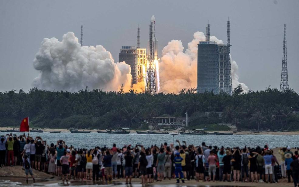 Chineses assistem ao lançamento de foguete do Centro de Lançamento Espacial Wenchang, na província de Hainan, sul da China, carregando o módulo central da estação espacial  — Foto: AFP Photo