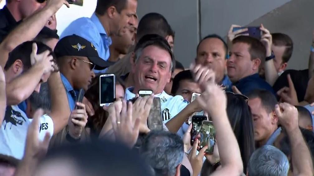 Bolsonaro veste a camisa do Santos e vai para o meio da torcida — Foto: Reprodução