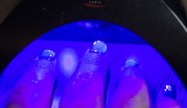Nail technician: nail care and semi-permanent nail polish set to harden under a UV lamp. (Photo by: Andia/Universal Images Group via Getty Images) (Foto: Universal Images Group via Getty)