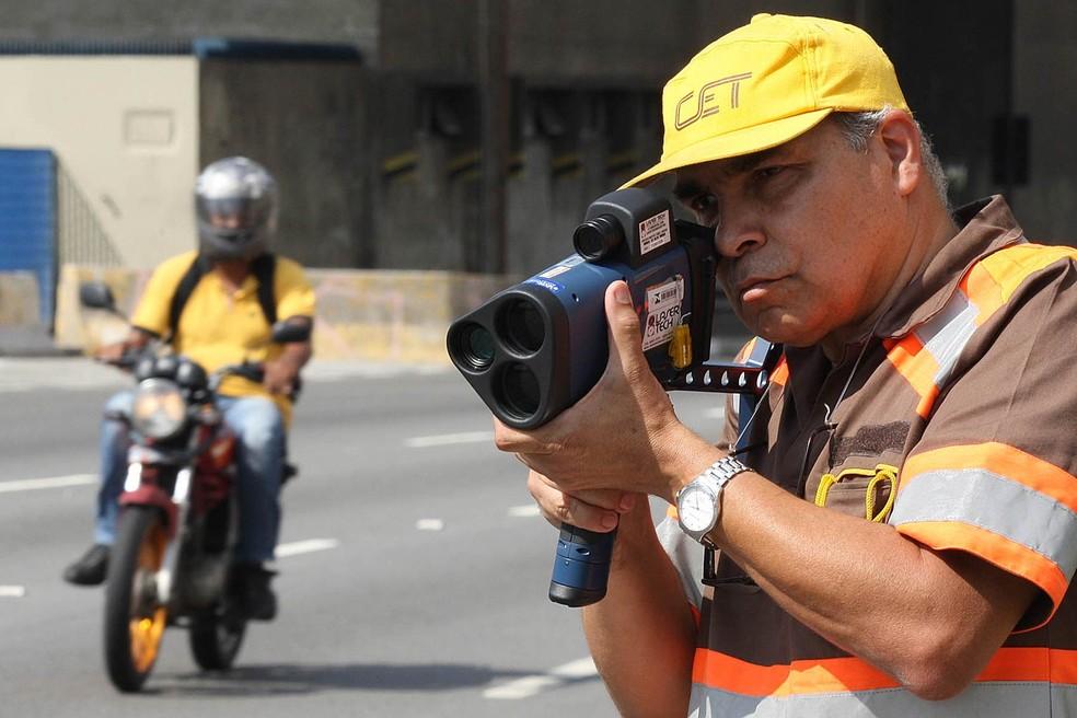 Agente da Companhia de Engenharia de Tráfego (CET) usa um radar-pistola para verificar a velocidade de motociclistas na Radial Leste (Foto: Márcio Fernandes/Estadão Conteúdo/Arquivo)