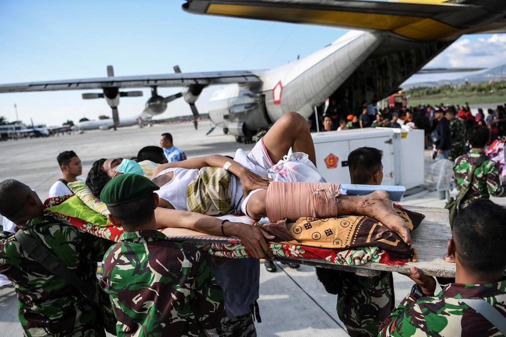 Um homem ferido é evacuado em um avião militar no Aeroporto de Palu, na Indonésia — Foto: REUTERS