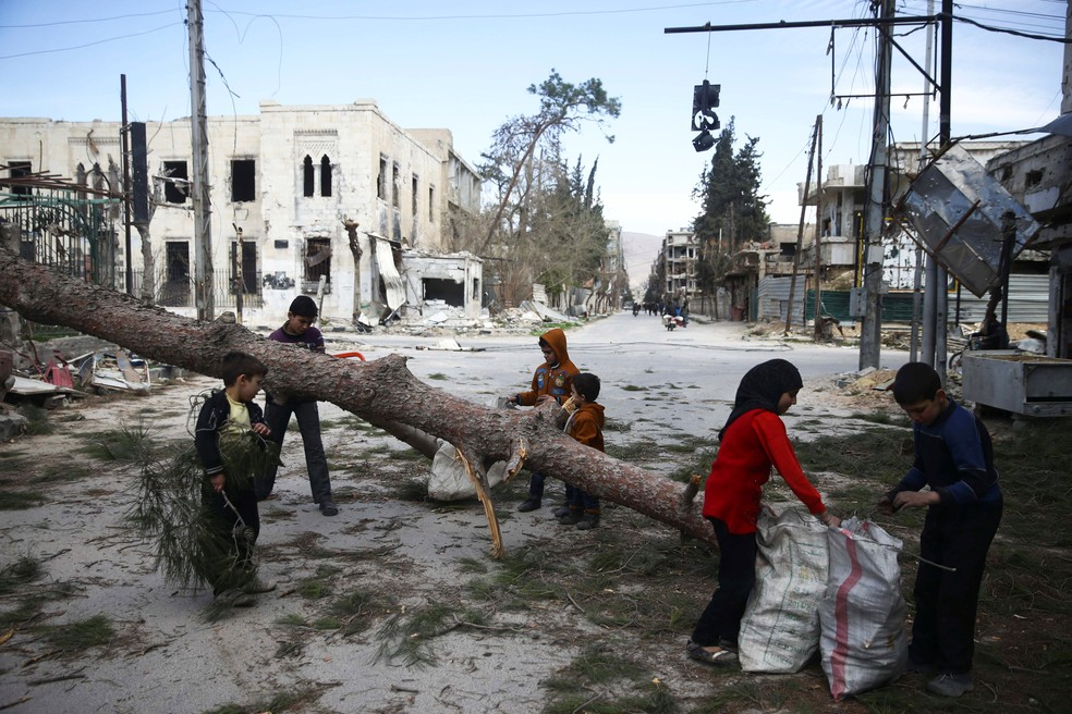 Crianças reúnem madeira em Guta na sexta-feira (9) (Foto: Bassam Khabieh/Reuters)