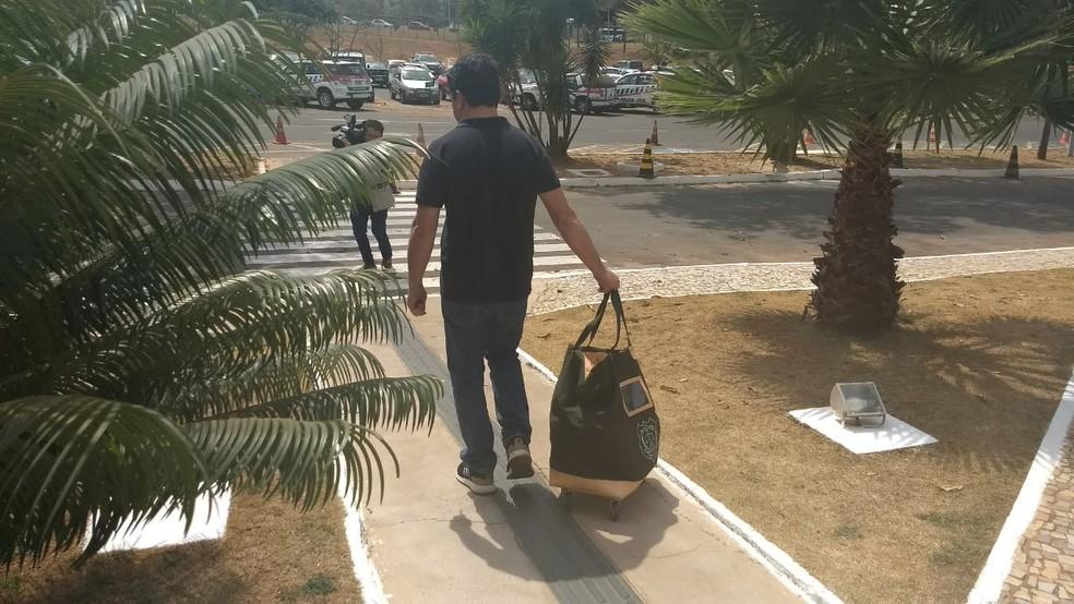 Agente da Polícia Civil carrega malote com documentos apreendidos (Foto: Elielton Lopes/G1)