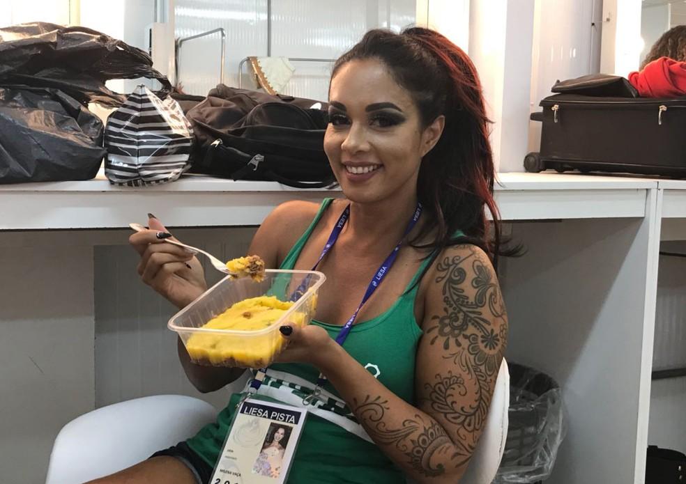 Milena Nogueira, rainha de bateria do Império Serrano, come marmita antes do desfile (Foto: Mateus Almeida / G1)