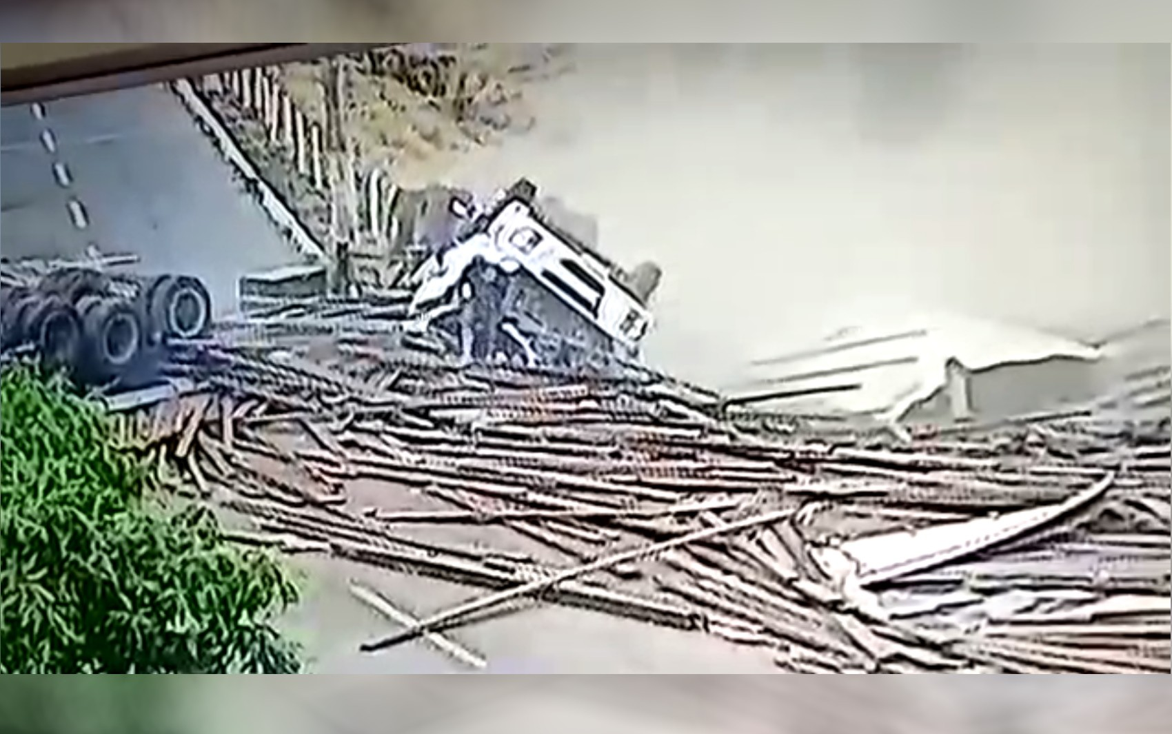 Motorista fica ileso e sai andando da cabine após caminhão tombar e espalhar carga de madeira pela GO-050; vídeo