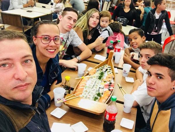 Com o marido, Lorenzo e Mateus (ao lado de Lorenzo), mais quatro dos cinco filhos dele (um dos meninos é genro) (Foto: Reprodução Facebook)
