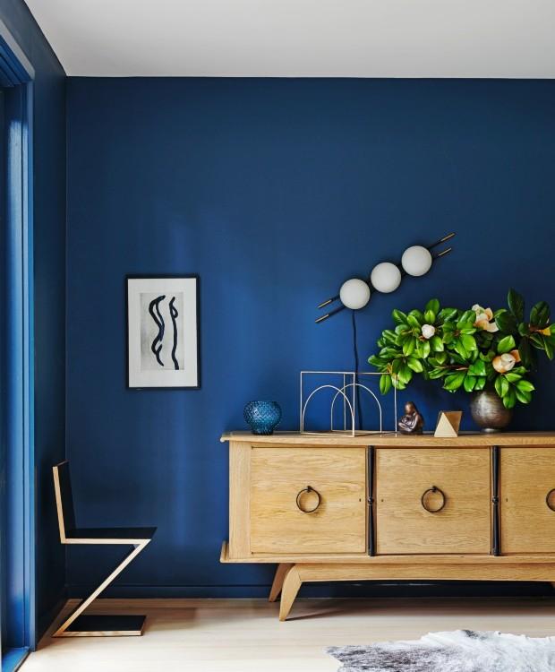 Equilíbrio. A escolha pela madeira clara no piso e no mobiliário, como o aparador da década de 1950, contrasta com o azul das paredes. Os objetos que compõem o interior são um mix de itens comprados em viagens e peças vintage (Foto: Lisa Cohen / Living Inside)