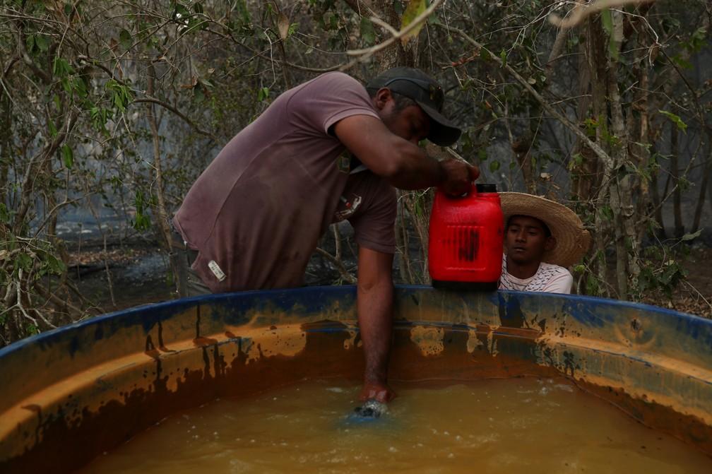 Carlos Augusto Rodrigues, de 35 anos, dá a Rafael Silva, de 16, uma garrafa cheia de água para ajudar a apagar um incêndio em uma fazenda no Pantanal — Foto: Amanda Perobelli/Reuters