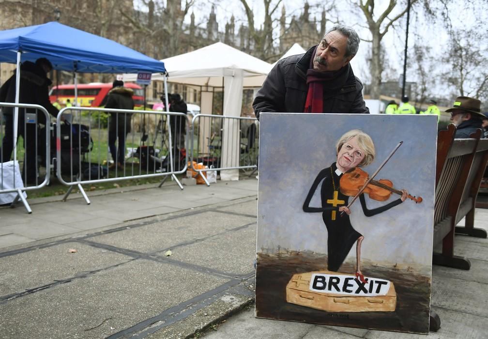 Após derrota do acordo do Brexit no Parlamento britânico, homem mostra pintura de Theresa May 'enterrando' o Brexit — Foto: Clodagh Kilcoyne/Reuters