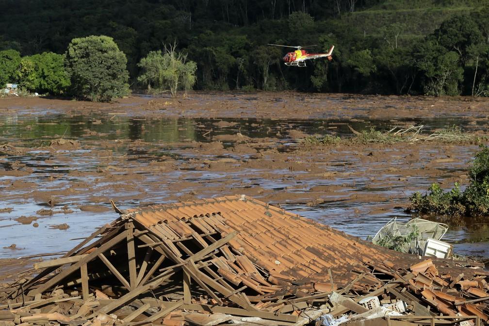 Equipes de resgate fazem busca de helicóptero em área inundada dois dias depois do rompimento da barragem da Vale, em Brumadinho. — Foto: André Penner/AP
