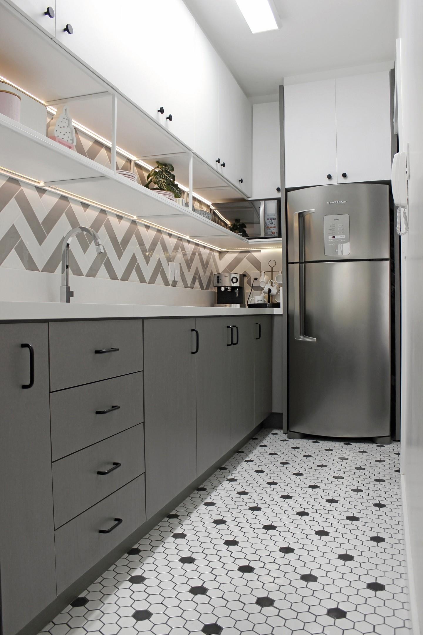 Cozinha pequena com piso de pastilhas, geladeira cinza, armários branco e cinza.