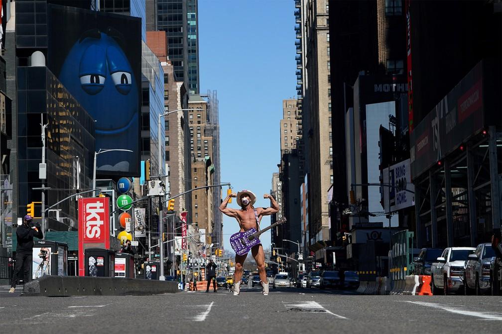 NOVA YORK (EUA) - Robert Burck, o artista de rua de NY conhecido como 'Naked Cowboy' (Caubói Pelado'), posa para fotos na Times Square com pouco movimento nesta terça-feira (24) — Foto: Carlo Allegri/Reuters