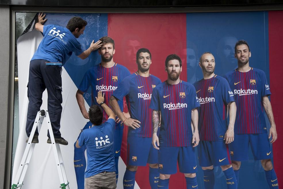 Funcionários no Camp Nou colam novos cartazes do Barcelona sem Neymar (Foto: AFP)