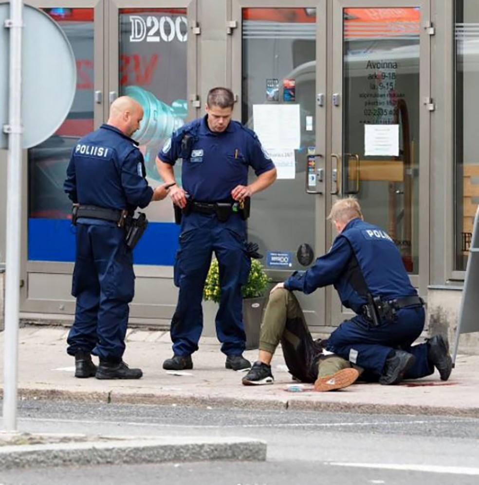Uma pessoa é atendida por policial no chão em Turku (Foto: KIRSI KANERVA / AFP)
