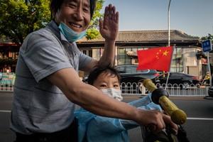 Homem e criança de máscara em Pequim