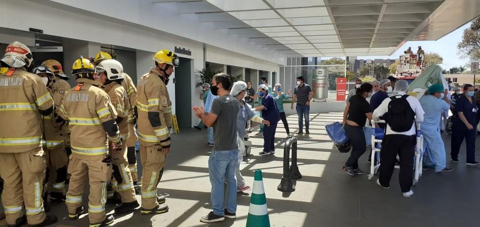 Bombeiros, parentes de pacientes e funcionários do Hospital Santa Luzia em frente ao prédio, durante incêndio — Foto: TV Globo/ Reprodução