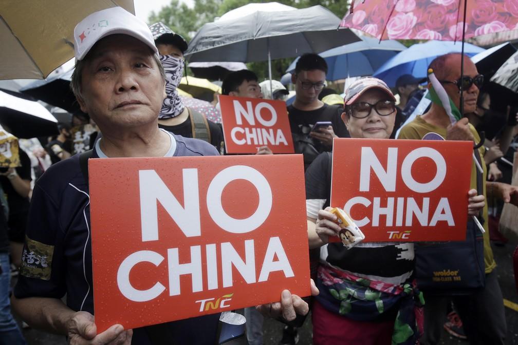 Em Taiwan, manifestantes seguram cartazes que dizem 'não à China' em protestos neste domingo (29) em Taipei. — Foto: Chiang Ying-ying/AP