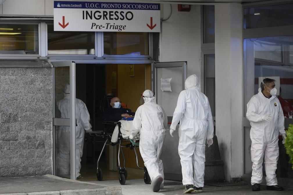 Funcionários entram em hospital de Nápoles, na Itália, com paciente em maca, nesta quinta-feira (12) — Foto: Filippo Monteforte/AFP