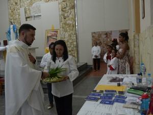 Padre abençoa carteiras de trabalho e currículos durante a missa (Foto: Maiara Barbosa/ G1)