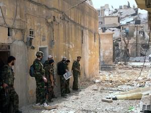 Soldados do exército da Síria patrulham o bairro de Karam al-Jabal (Foto: AFP)
