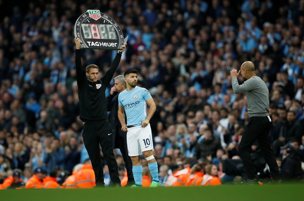 Com proteção no joelho, Aguero conversa com Guardiola antes de entrar no clássico contra o United (Foto: Reuters)