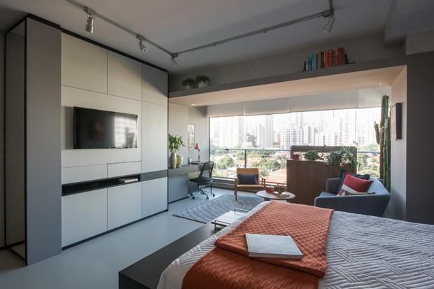 Apartamento de 39 m² com estilo industrial tem sala de estar na varanda (Foto: Divulgação)