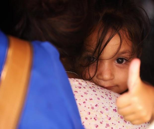Criança migrante faz sinal de positivo para o fotógrafo (Foto: Héctor Alfaro)