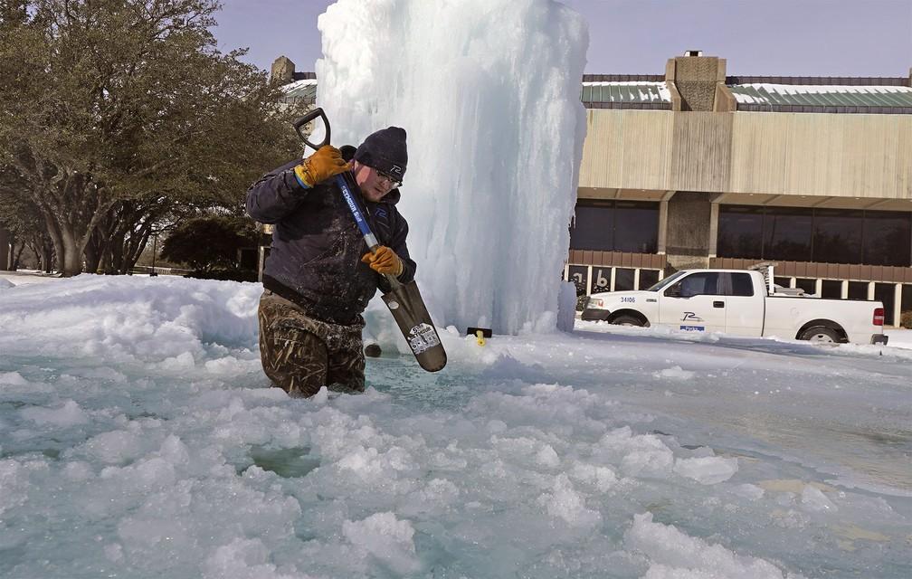 Kaleb Love usa uma pá para quebrar o gelo de uma fonte congelada em Richardson, Texas — Foto: LM Otero/AP