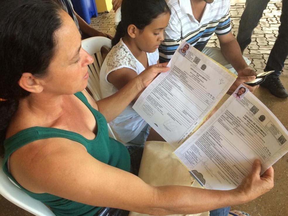 Maria Aparecida mostra documentos dela e da filha — Foto: Tahiane Stochero/G1