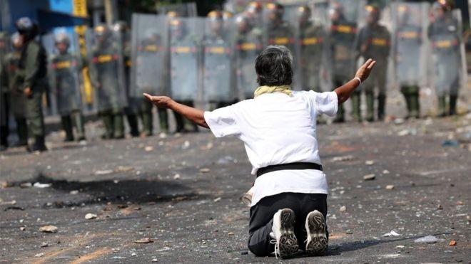 Um manifestante se ajoelha diante das forças de segurança na fronteira da Venezuela com a Colômbia (Foto: Reuters via BBC)